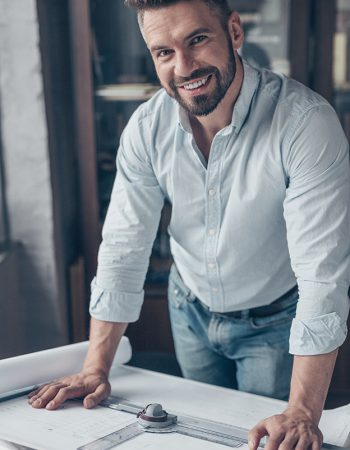 Smiling mature man with drawing in the workplace